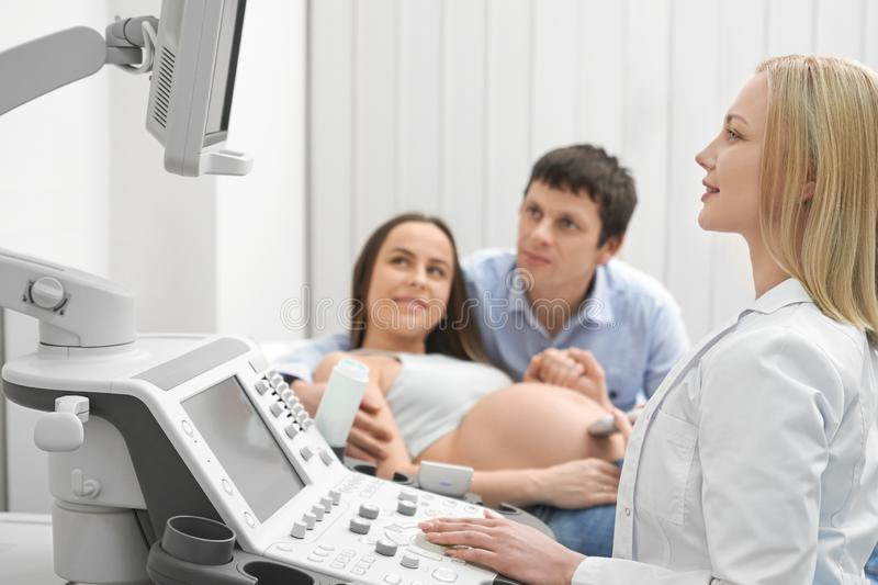 Future mother with husband on ultrasound exam in clinic. royalty free stock photos