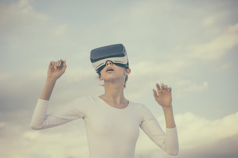 Future is now. Young woman gesturing in vr glasses. Pretty girl wear virtual reality headset. Cute girl play in. Simulated environment. Innovative vr technology royalty free stock images