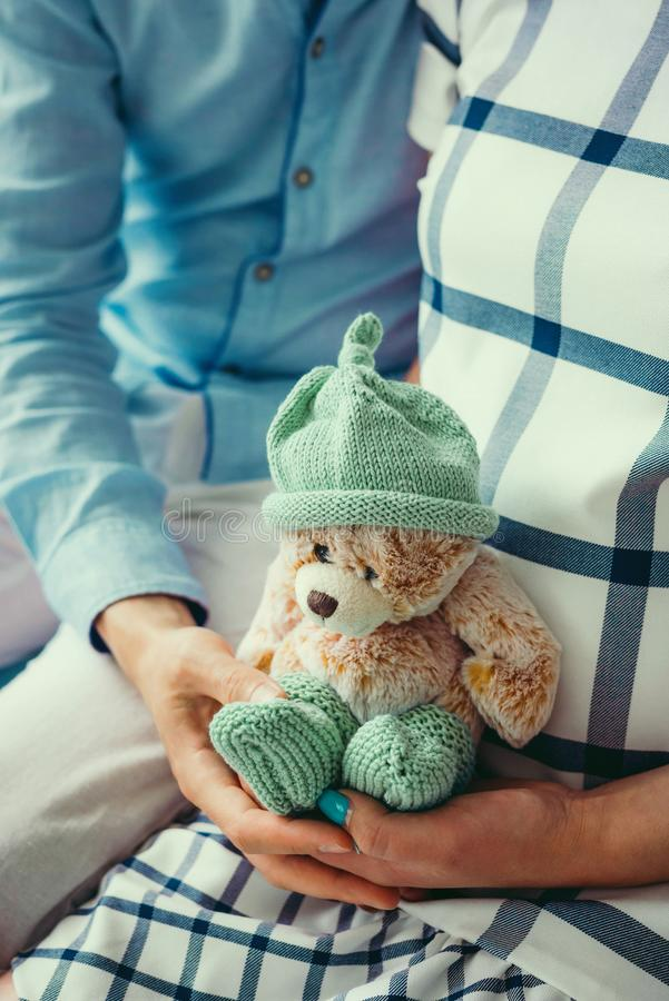 Future parents are holding the small lovely teddy bear in green knitted socks and hat. No face. Close-up shot stock photo