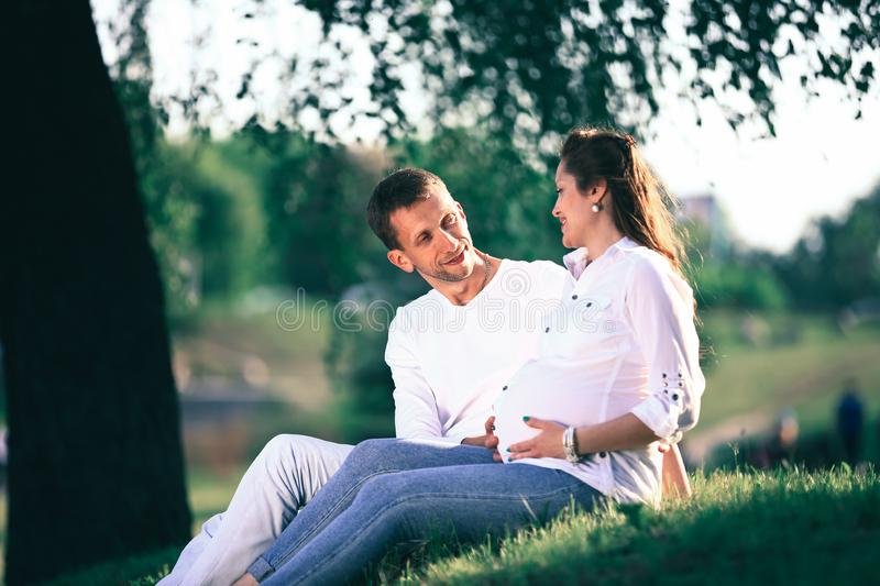 Future parents sitting on the grass in the Park on a Sunny day. royalty free stock photos
