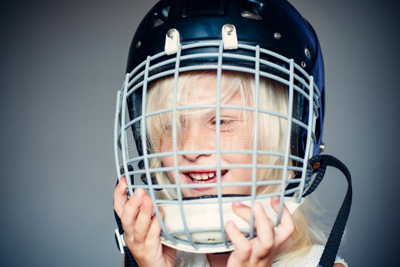 Future sport star. Sport upbringing and career. Girl cute child wear hockey helmet close up. Safety and protection royalty free stock image
