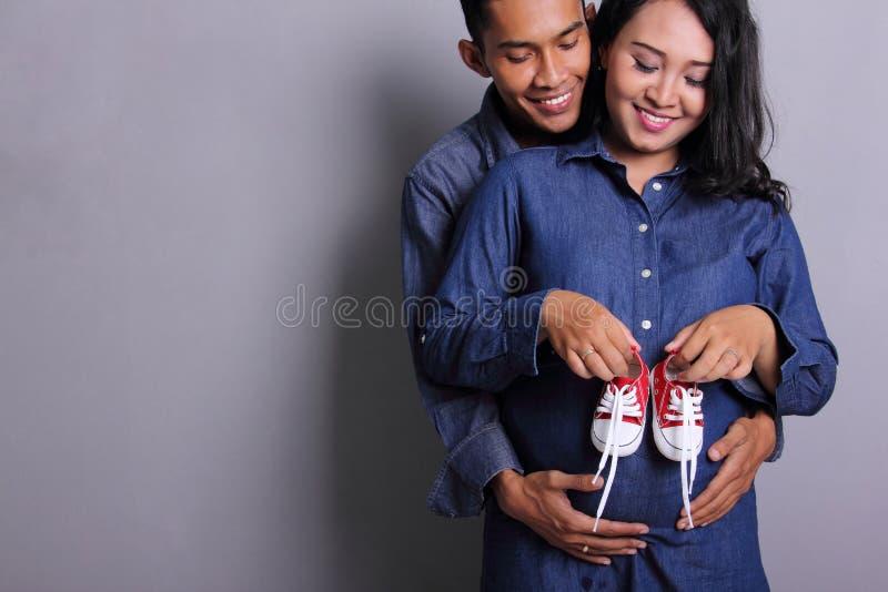 Futuri genitori e scarpe di bambino felici fotografia stock