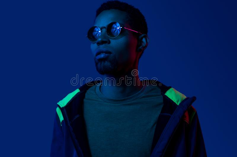 Futuristic portrait of black young man in sunglasses stock photography