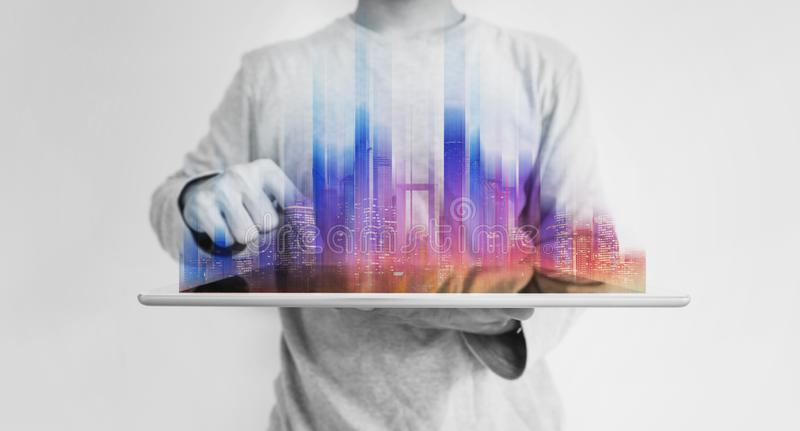 Futuristic man holding digital tablet with colorful modern building hologram. On white background royalty free stock images