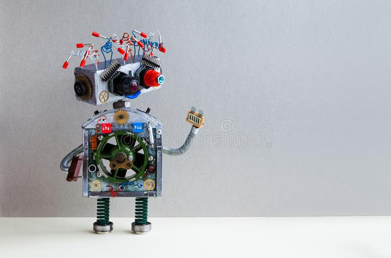 Futuristic robot electrical wire hairstyle, plug arm. Creative design robotic toy mechanism, funny head, colored blue. Red eyes. Copy space, gray wall stock images