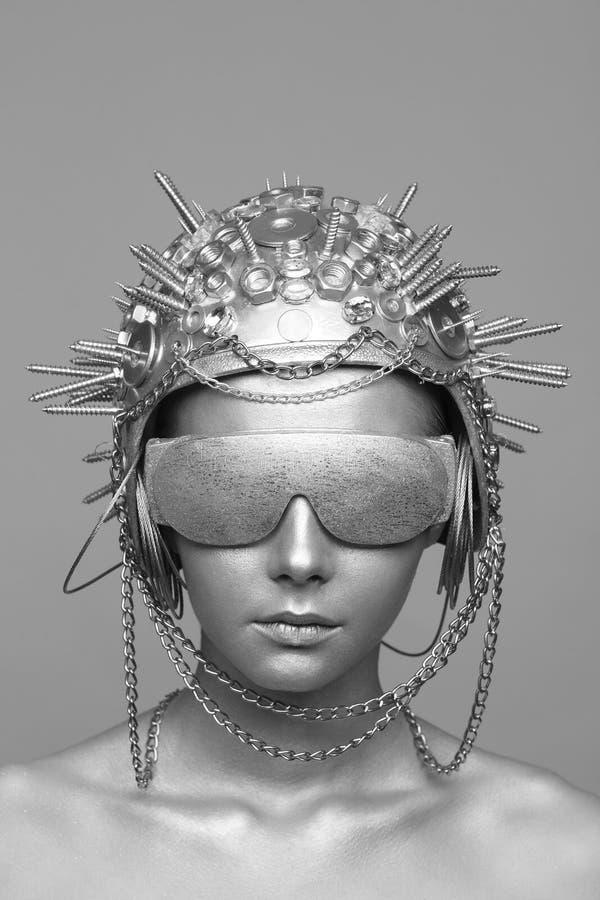 Futuristic woman in metal helmet and glasses stock image