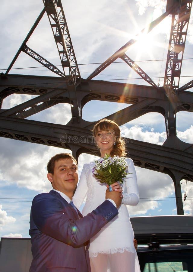 Futuristisch portret van bruid en bruidegom in zonstralen op de brug royalty-vrije stock afbeelding