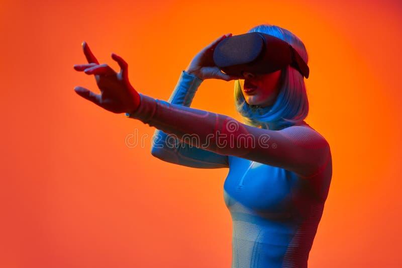 Futuristische Dame, die auf virtuelle Realit?t einwirkt stockfotos