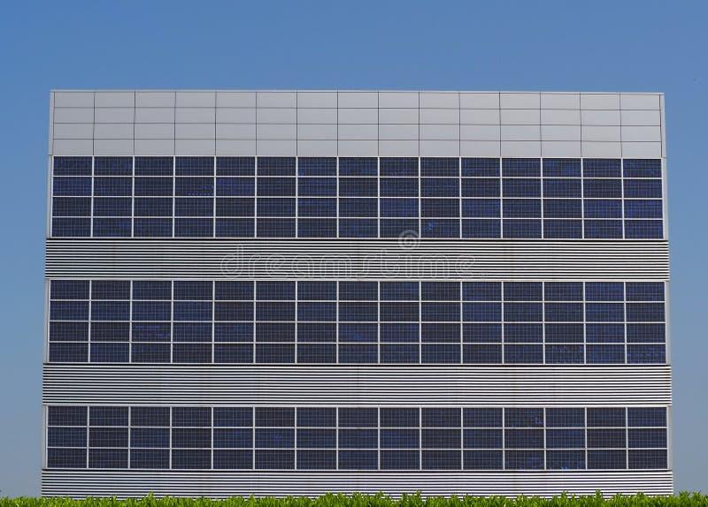 Futuristische unbedeutende Gebäudefassade gemacht von der Aluminiumumhüllung und von den Sonnenkollektoren stockbild