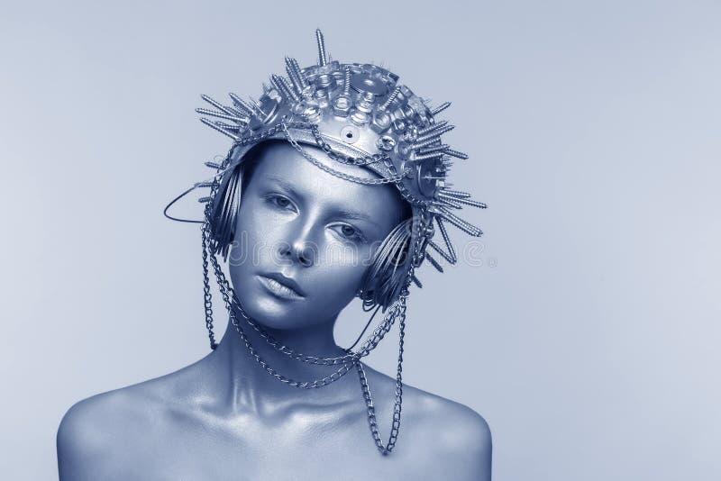 Futuristische vrouw in metaalhelm met schroeven, noten en kettingen royalty-vrije stock afbeelding