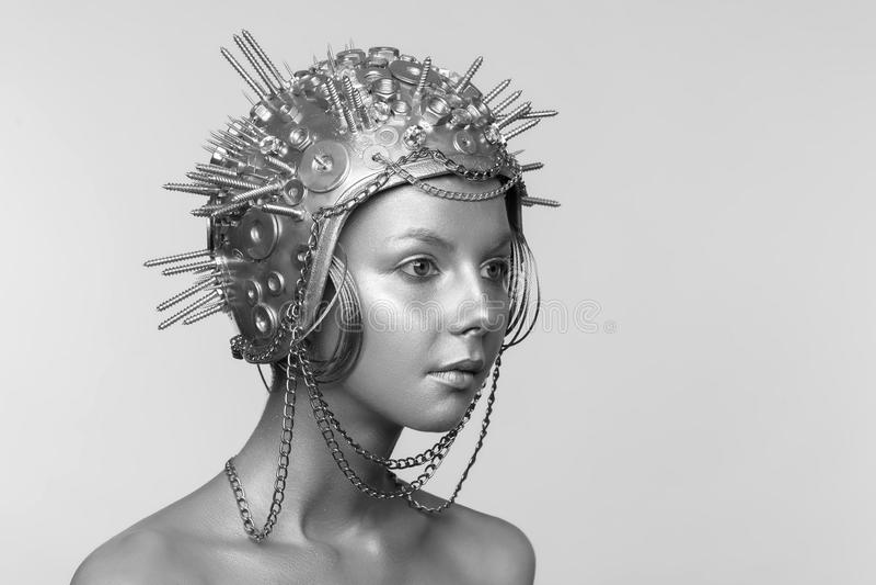Futuristische vrouw in metaalhelm met schroeven, noten en kettingen royalty-vrije stock afbeeldingen