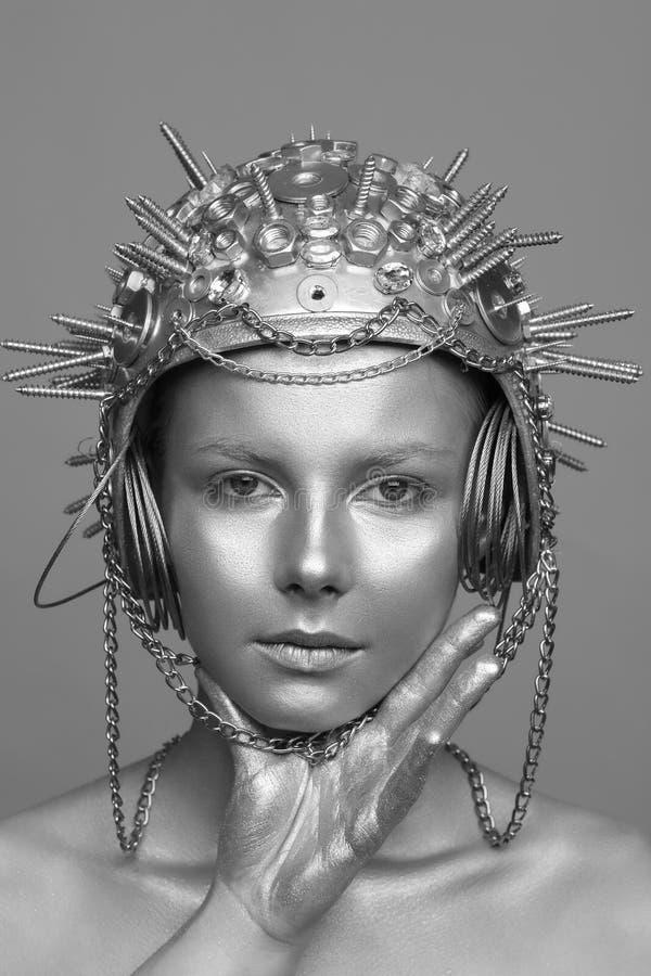 Futuristische vrouw in metaalhelm met schroeven, noten en kettingen stock foto's