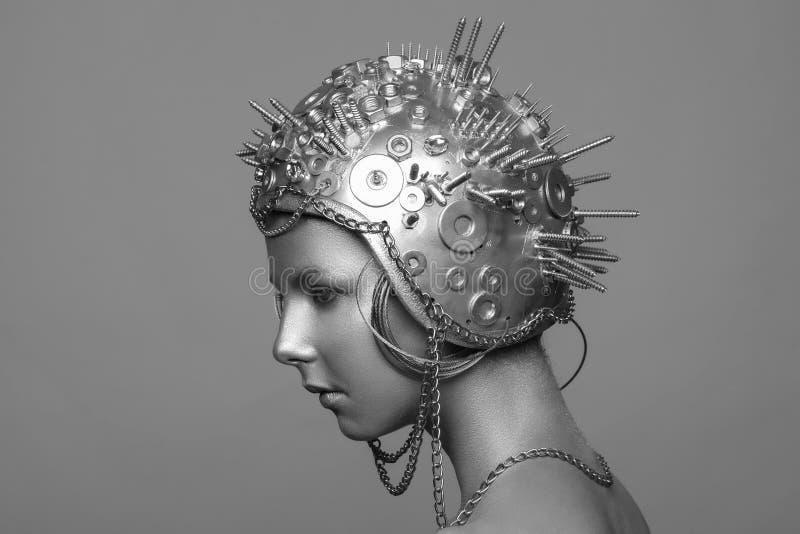 Futuristische vrouw in metaalhelm met schroeven, noten en kettingen stock foto