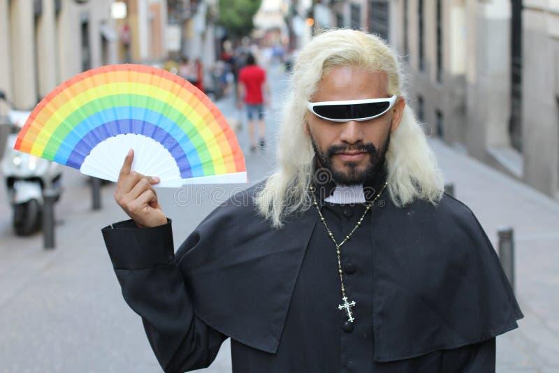 Futuristischer schauender Priester, der einen Regenbogenfan h?lt lizenzfreie stockfotografie