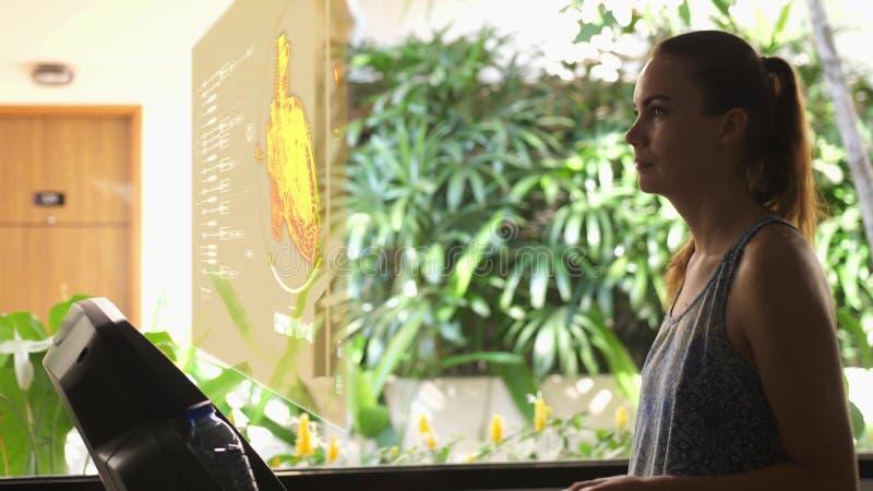 Futuristisches Porträt einer jungen Schönheit im Turnhalle onxtreadmill benutzt ein Hologramm mit Herzherzschlag stockfotos