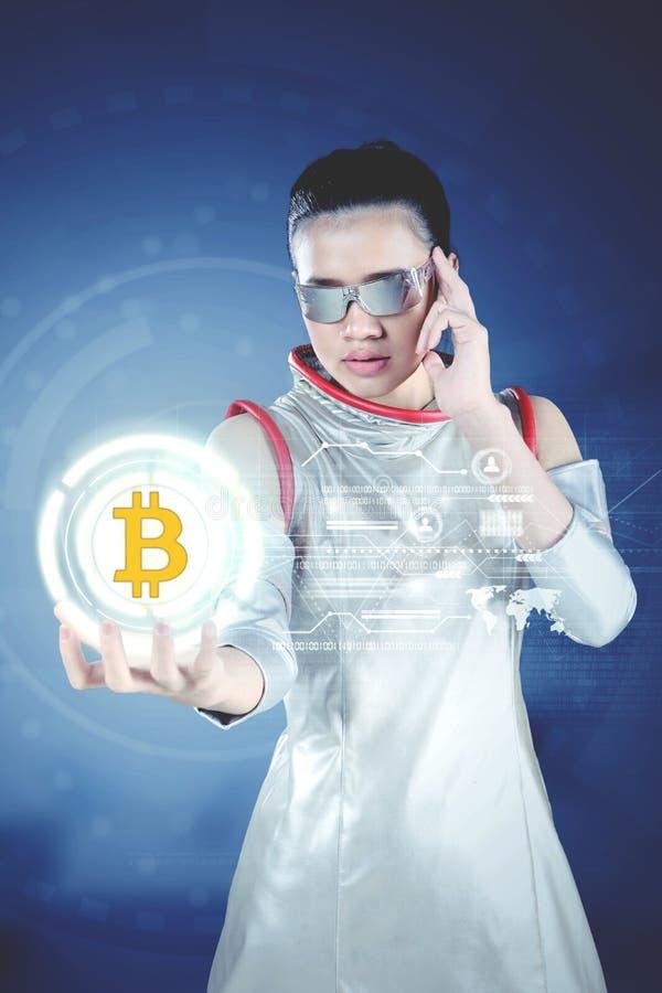 Futuristisk kvinna som visar ett faktiskt bitcoinsymbol arkivbild