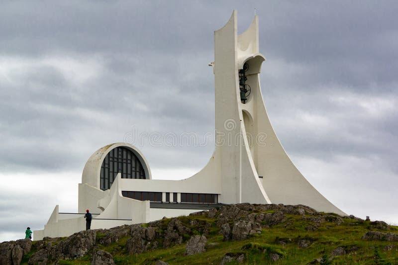 Futuristisk kyrka för Stykkishà ³lmskirkja i Stykkishà ³lmur, Island i molnigt väder fotografering för bildbyråer