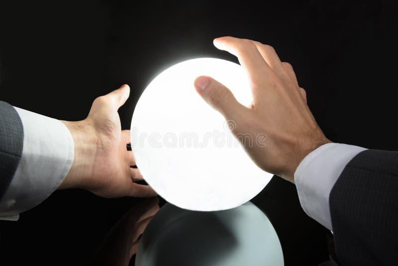 Futuro di predizione della mano del ` s dell'uomo d'affari con Crystal Ball immagini stock