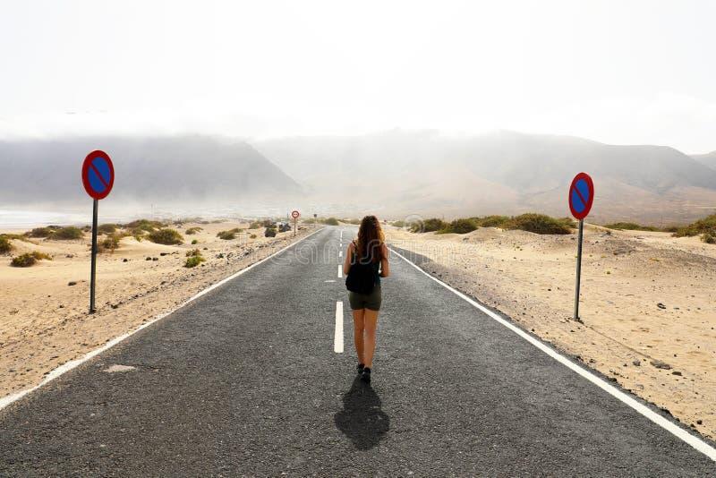 Futuro incerto A mulher sozinha nova avança com uma etapa incerta na estrada vazia do deserto do asfalto Conceito do apocalipse fotos de stock