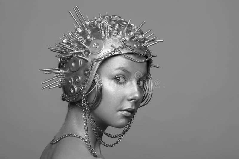 Futurystyczna kobieta w metalu hełmie z śrubami, dokrętkami i łańcuchami, zdjęcie royalty free