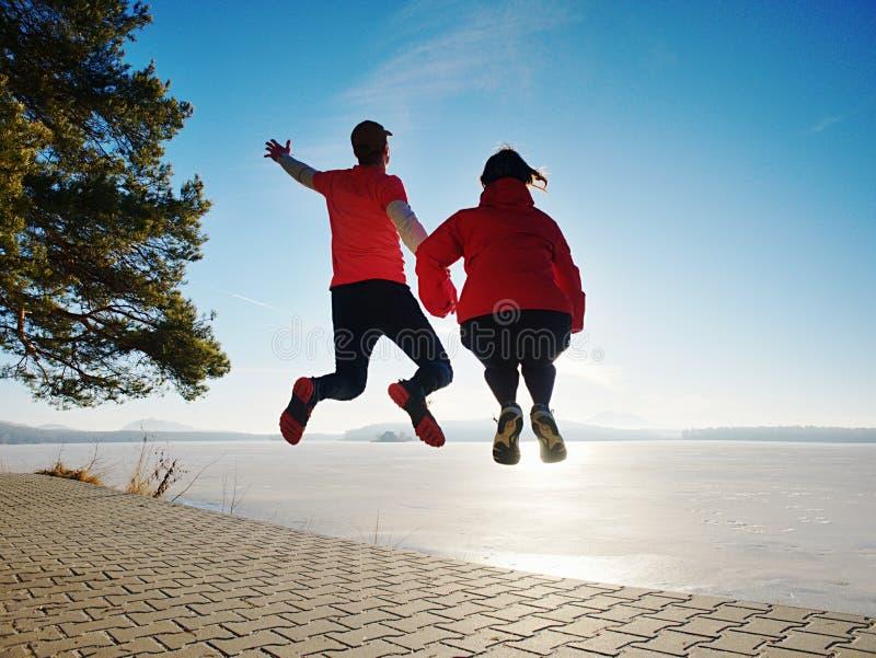 Fuuny szczęśliwi kochankowie skaczą wpólnie Kobieta ręka w rękę i mężczyzna obrazy royalty free