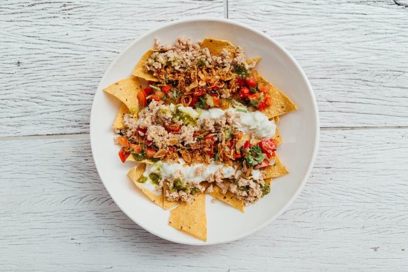 Fuzji jedzenie: Odgórny widok Soboro kurczaka Nachos: Styl smażący kurczak z pomidorowym salsa, jogurt obrazy royalty free