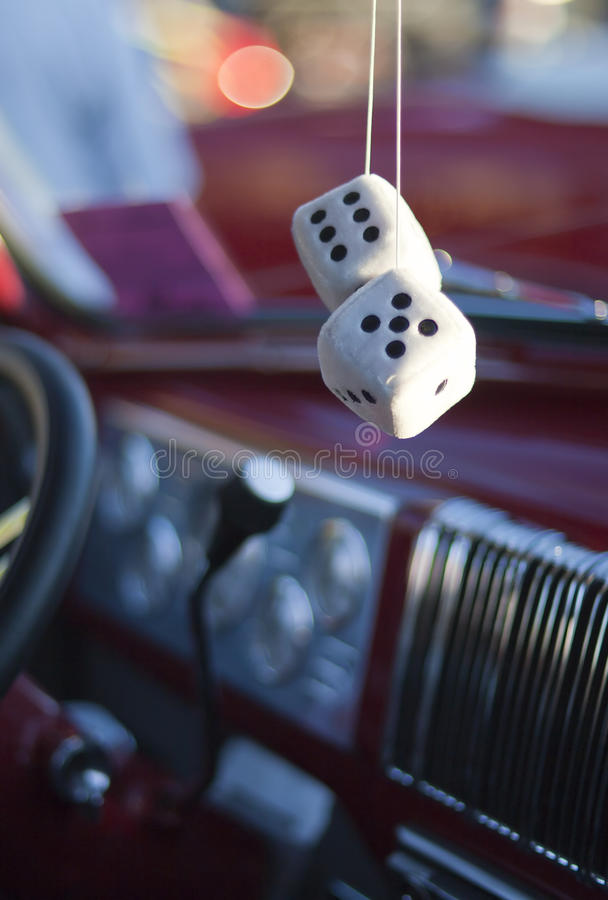 Fuzzy Dice. Hanging in classic car interior stock photography