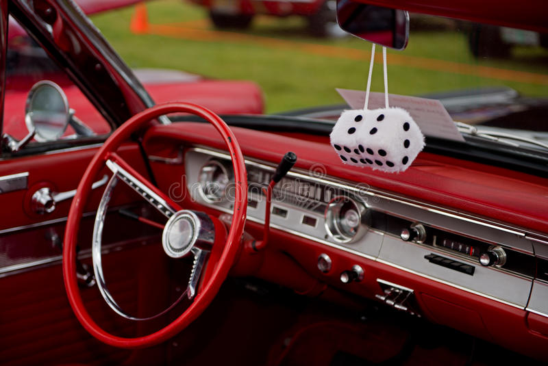 Fuzzy Dice. Abstract of a retro 1960's style convertible with red interior and black exterior and a pair of fuzzy dice hanging from the rear view mirror stock image