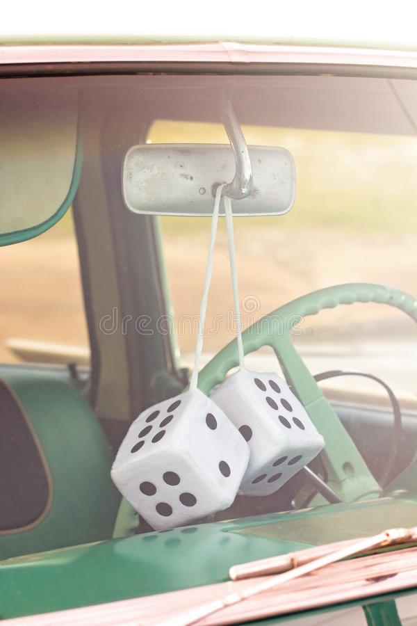 Fuzzy Dice Hanging from the Rearview Mirror of an Antique Car stock photography