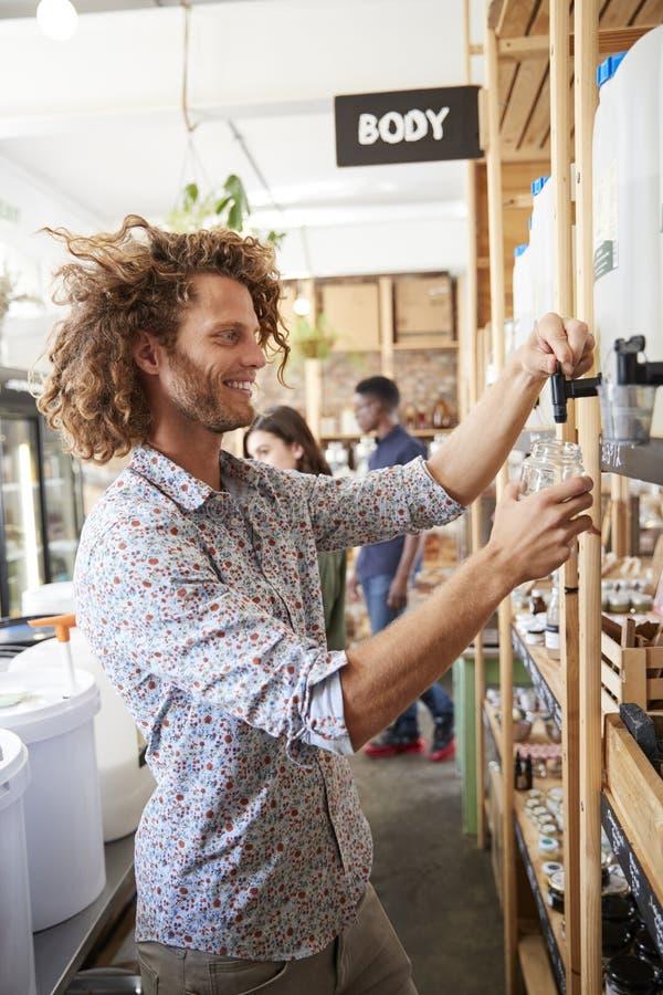 Fyllande behållare för man med diskarePowder In Plastic den fria livsmedelsbutiken royaltyfri bild
