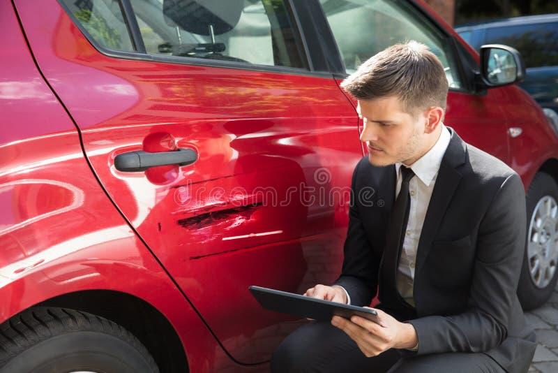 Fyllande försäkringform för man nära den skadade bilen royaltyfria bilder