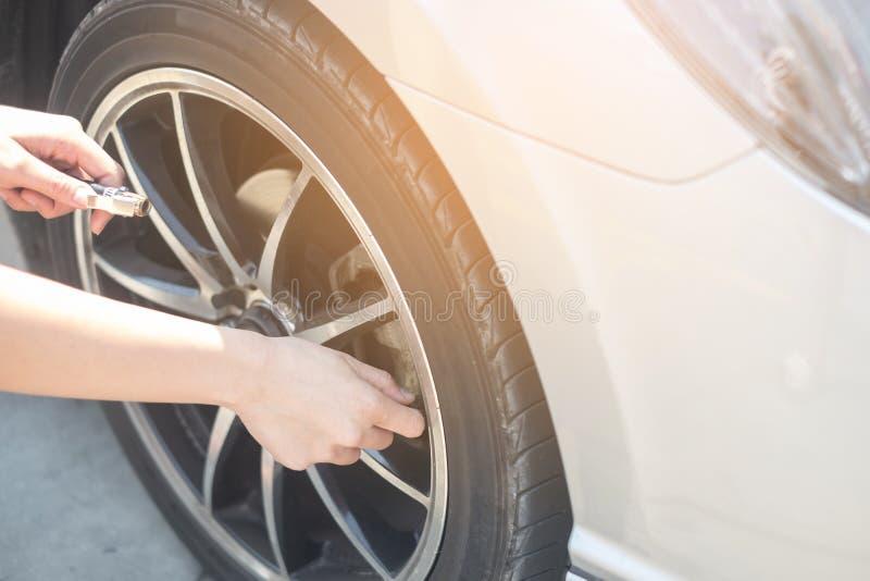 Fyllande luft för asiatisk kvinna in i ett bilgummihjul som ökar tryckbilgummihjulet royaltyfri fotografi