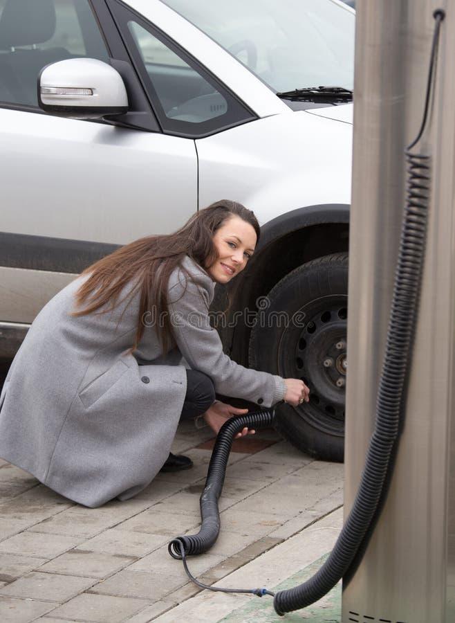 Fyllande luft för kvinna i gummihjul av bilen arkivfoto