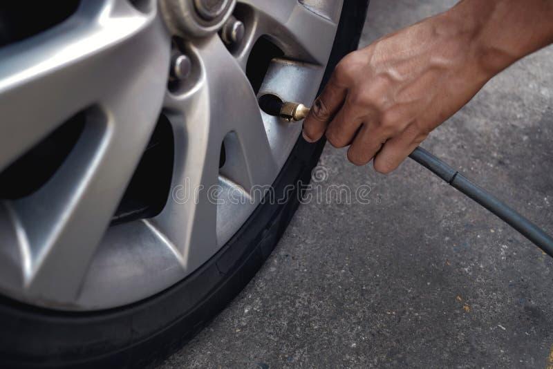 Fyllande luft för man in i gummihjulet Bilchaufför Checking Air Pressure och underhåll hans bil vid honom royaltyfria foton