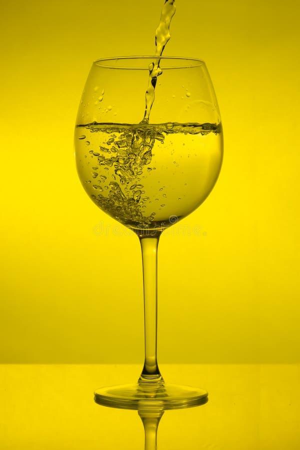 Fyllande vinexponeringsglas på gul bakgrund, hällande vinglas arkivbild