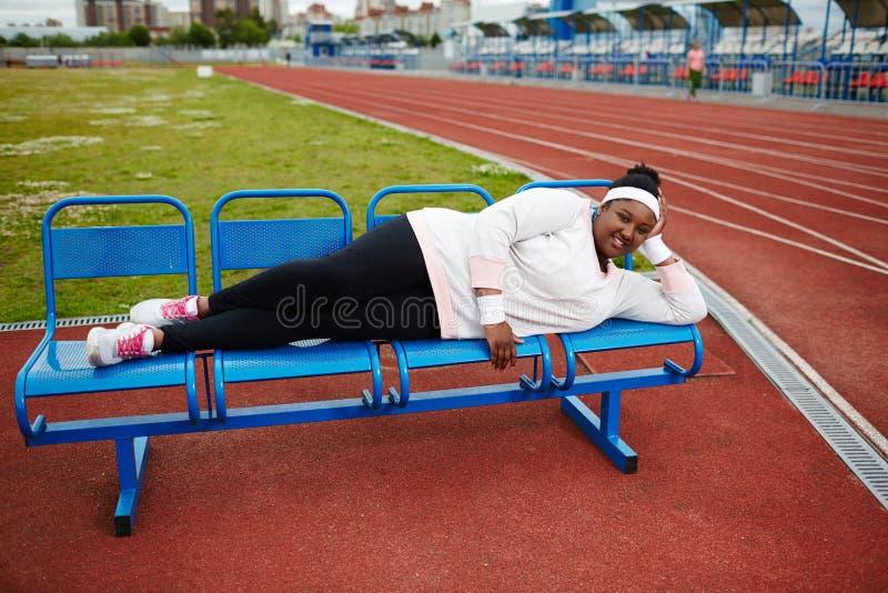 Fyllig afrikansk kvinna som ligger på bänk, når att ha övat på friidrottstadion fotografering för bildbyråer