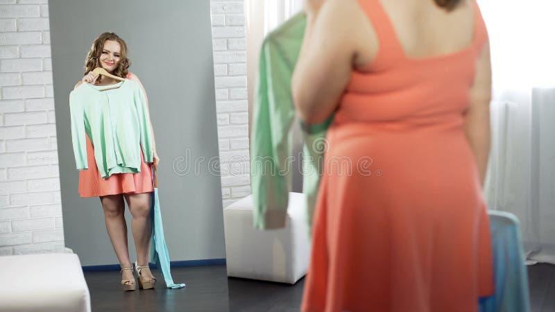 Fyllig flicka som väljer kläder i loge, plus formatmode, kropprealitet fotografering för bildbyråer
