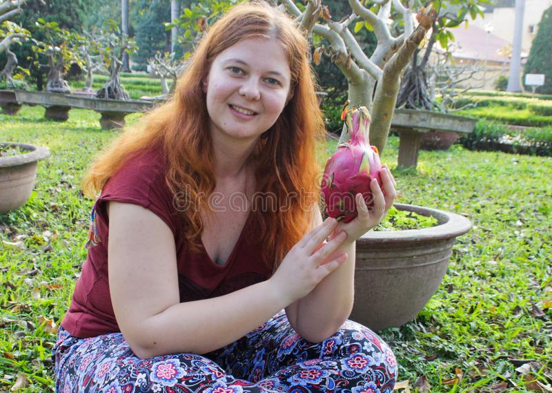 Fyllig vit flicka som rymmer en exotisk pitahaya för tropisk frukt royaltyfria foton