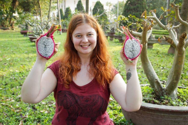 Fyllig vit flicka som rymmer en exotisk pitahaya för tropisk frukt royaltyfri fotografi