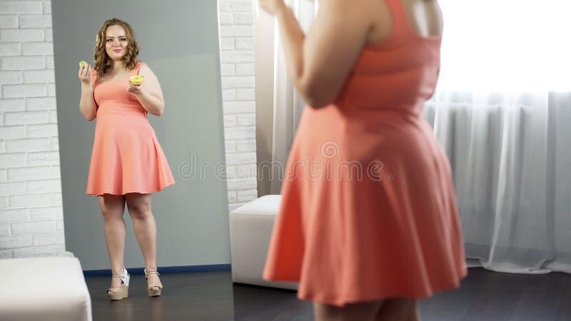 Fylliga kvinnliga hållande söta donuts som är främsta av spegeln, tillfredsställt med hennes blick arkivfoto