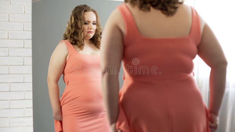 Fylligt kvinnligt se i spegel, rubbning om hennes buk, överviktiga osäkerheter royaltyfri fotografi