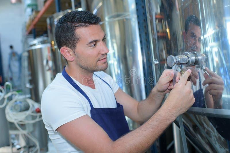 Fyllnads- öl för producent in i exponeringsglas från lagringsbehållare på bryggeriet royaltyfria bilder