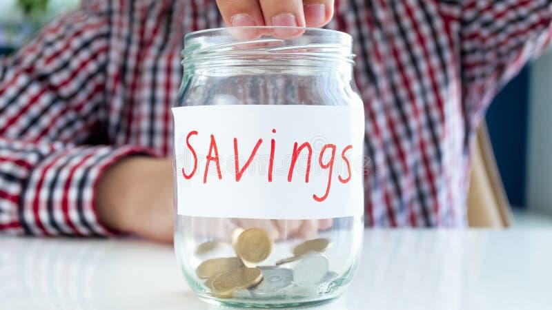 Fyllnads- familjbudget för ung man Closeupfoto av den manliga handen som kastar mynt i den glass kruset med besparingar arkivfoto