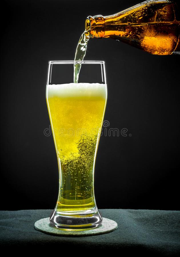 Fyllnads- glass exponeringsglas med guld- öl på slut upp royaltyfri bild