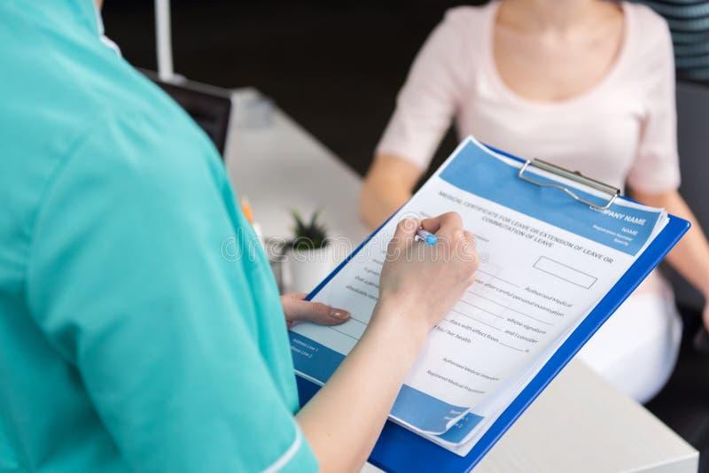 Fyllnads- medicinsk form för internist medan tålmodigt sammanträde bakom i klinik royaltyfri fotografi