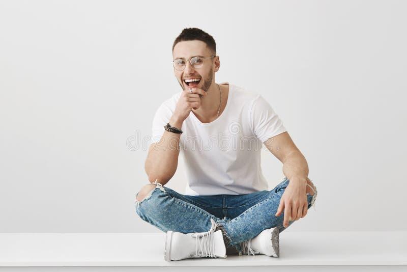 Fyndvänner som ska göra dig att skratta Stående av den snygga känslobetonade mannen med avkänning av stilsammanträde på golv med royaltyfri foto
