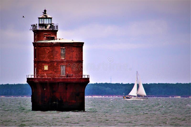 fyr på Chesapeke Bay med en segelbåt i bakgrunden royaltyfri fotografi