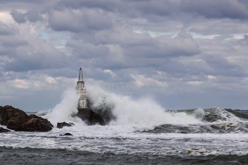 Fyr på klippan och de stora vågorna arkivbilder