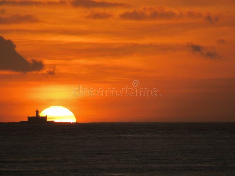 Fyr på solnedgången: Djup orange himmel arkivfoto