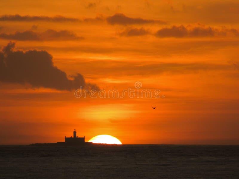 Fyr på solnedgången: Djup orange himmel arkivfoton